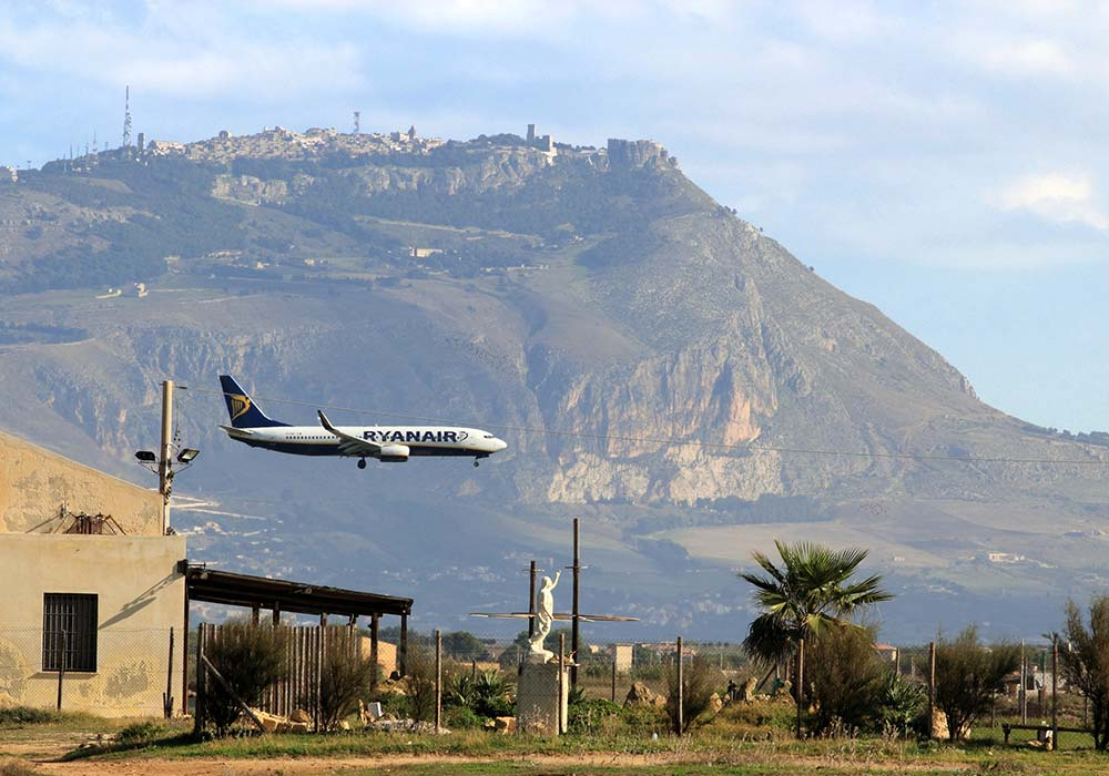 A Ryanair plane with the medieval town of Erice in the background