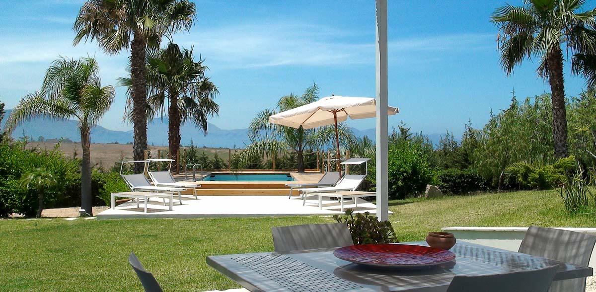 Het zwembad en de tuin gezien vanaf het terras van Appartamento Chistu